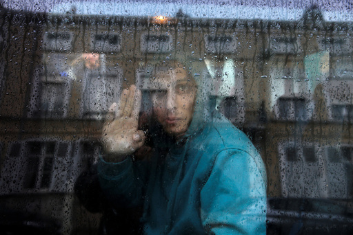 An Afghan adolescent migrant waves from a van as he departs with six others from the emergency shelter for minors in Saint Omer