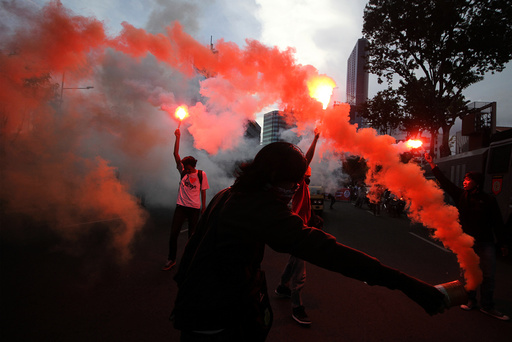 Workers hold fireworks during a protest marking May Day in Surabaya