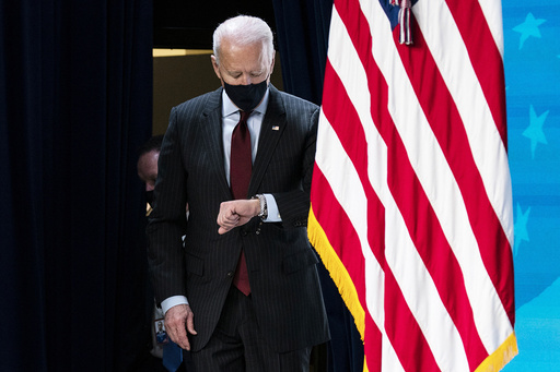 President Joe Biden checks his watch as he arrives to speak about the Paycheck Protection Program during an event in the South Court Auditorium on the White House campus, Monday, Feb. 22, 2021, in Washington. (AP Photo/Evan Vucci)