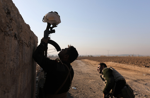 An Iraqi soldier uses his rifle to hold up a helmet as a decoy during clashes with Islamic State fighters in Al-Qasar, South-East of Mosul