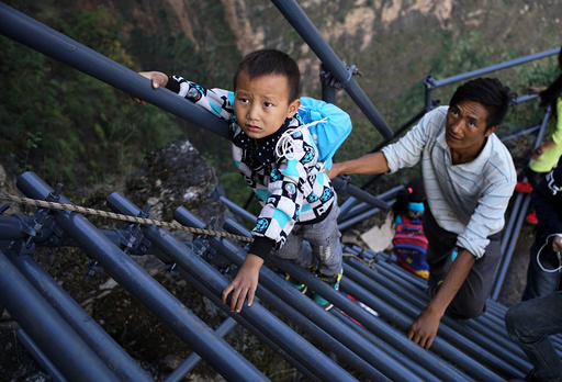 A student from the cliff village in Atule'er climbs newly-constructed steel ladders after school to go home for holidays, in Liangshan