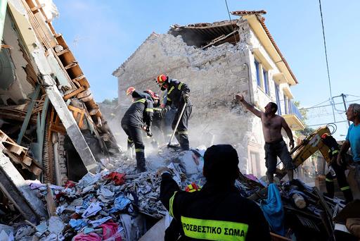 Rescue team members search for victims at a collapsed building in the village of Vrissa on the Greek island of Lesbos