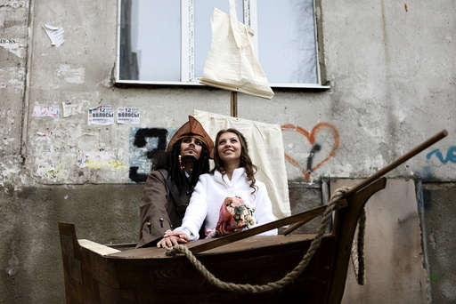 Krasitsky from Russia dressed as movie character Captain Jack Sparrow and his bride Anastasiya pose with a sailing ship decoration during their wedding ceremony in Stavropol