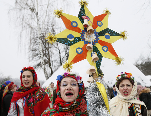 Women dressed in traditional costumes sing Christmas carols as they gather to celebrate the Orthodox Christmas at a compound of the National Architecture museum in Kiev