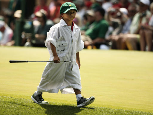 U.S. golfer Tiger Woods' son Charlie carries one of his father's clubs along the fourth hole during the par 3 event held ahead of the 2015 Masters at Augusta National Golf Course in Augusta