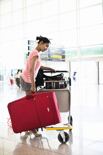 Woman putting suitcase on luggage cart in airport lounge