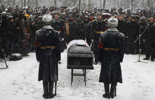 Members of an honor guard stand at attention next to the coffin holding the body of Oleg Peshkov, a Russian pilot of the downed SU-24 jet, during a funeral ceremony at a cemetary in Lipetsk