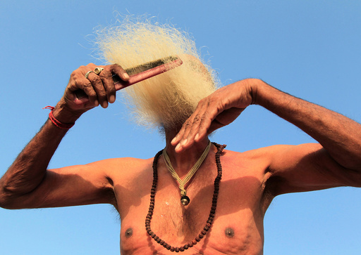 A Sadhu or Hindu holy man combs his beard after taking a dip in the waters of Shipra river during Simhastha Kumbh Mela in Ujjain