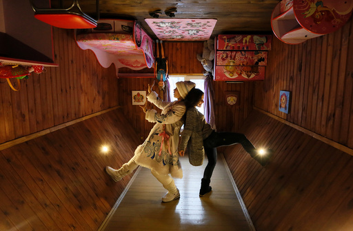 A visitor and an employee dressed as Snegurochka pose for a picture inside an upside down house at the Royev Ruchey Park of Flora and Fauna in the suburbs of Krasnoyarsk