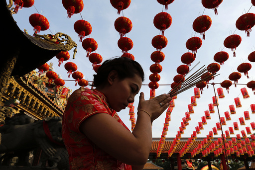 A woman prays in a temple decorated to celebrate Chinese New Year at Samut Prakan province outside Bangkok