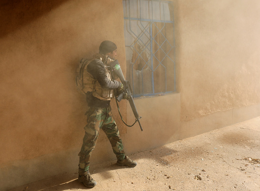 An Iraqi soldier searches a house during clashes with Islamic State fighters in Al-Qasar, South-East of Mosul