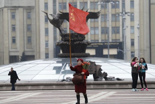 A communist woman walks with a communist flag and flowers in the center of in Minsk to celebrate the International Women's Day