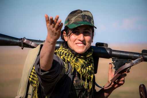 A Kurdish female fighter from the YPG gestures as she carries her weapon near the al-Hawl area where fighting between Islamic State fighters and fighters from Democratic Forces of Syria are taking place in south-eastern city of Hasaka