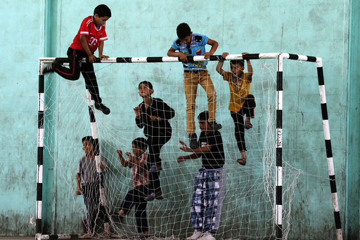 Refugee children play before start of a soccer match in the Al-Baqaa Palestinian refugee camp, near Amman