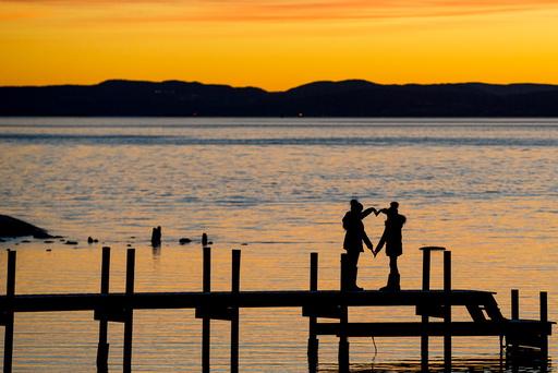 To unger former et hjerte i solnedgang ved Huk på Bygdøy fredag ettermiddag.