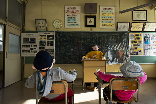 Scarecrows representing pupils and a teacher sit in a classroom in a closed down school in the village of Nagoro