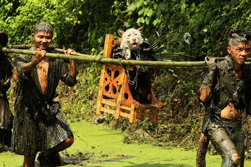 Men carry a dog during a local festival for the Miao ethnic minority in Jianhe county