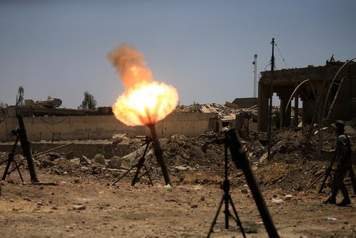 A member of the Iraqi rapid response forces fire mortar shells towards Islamic State militants during a battle with Islamic State militants in al-Zanjili neighborhood