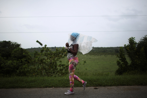 Naomi Rivera, 41, shields herself from the rain ahead of the arrival of Hurricane Matthew in Guantanamo, Cuba