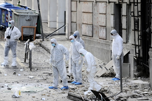 Forensic experts search for evidence on a street where a bomb exploded outside the entrance of the Hellenic Business Federation offices in Athens