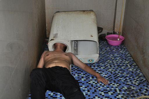 A man lies on the ground as his head is stuck in a washing machine in Fuqing county of Fuzhou
