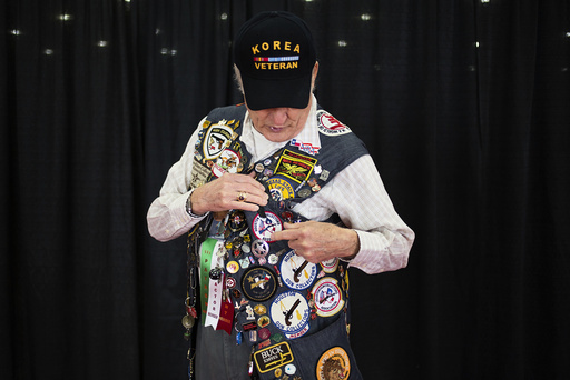 NRA lifetime member Lee Smith, 79, from Houston, shows off his pins and patches to event attendees while taking part in the National Rifle Association's annual meeting in Houston, Texas