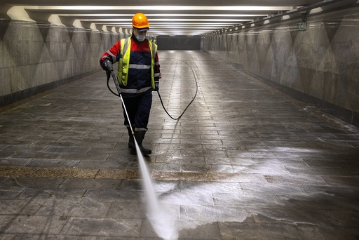 A municipal worker wearing a face mask to protect against coronavirus disinfects an empty underground crossing in Moscow, Russia, Saturday, Sept. 26, 2020. Moscow authorities have issued a recommendation for the elderly to stay at home and for employers to allow as many people as possible to work remotely, following a rapid growth of the coronavirus caseload in the Russian capital. He urged people over 65 and those suffering from chronic illnesses to stay at home starting from Monday, limit their contacts and leave their residence only when necessary. (AP Photo/Alexander Zemlianichenko)