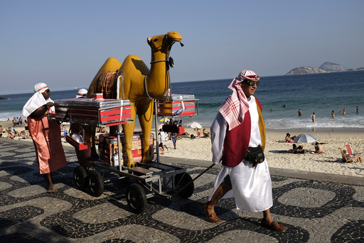 Street vendors in traditional Arabic outfits walk at Ipanema beach in Rio de Janeiro