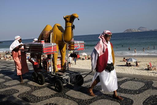 Street vendors in traditional Arabic outfits walk at Ipanema beach in Rio de Janeiro