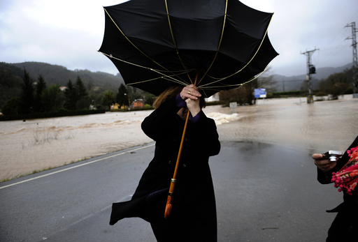 A woman attempts to hold onto her umbrella at a road partially submerged from floodwaters in Quinzanas, near Oviedo