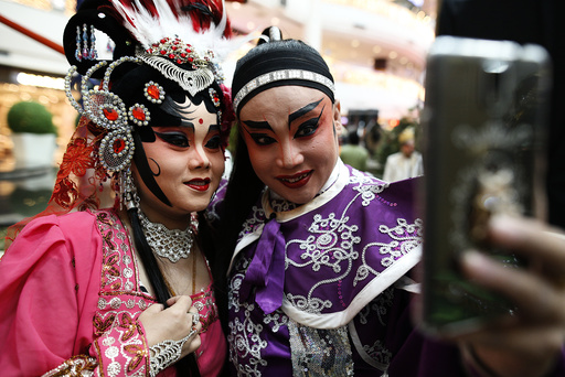 Members of a Chinese opera take a selfie before a performance at a shopping mall ahead of the Chinese Lunar New Year celebrations in Bangkok