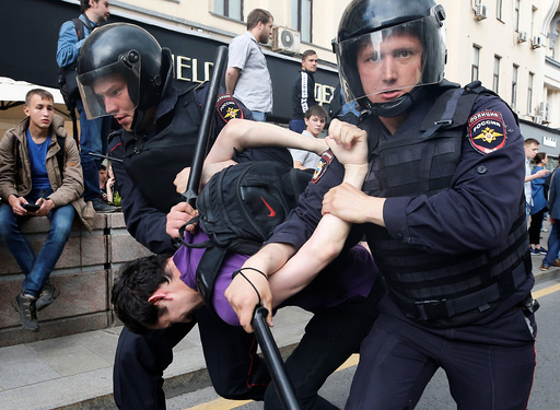 Riot police detain a man during an anti-corruption protest in central Moscow