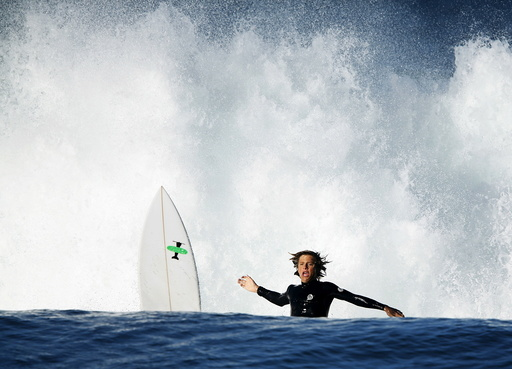 A surfer wipes out while trying to ride a breaking wave during high tide and high surf in Cardiff, California