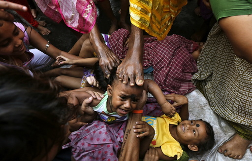A child cries as a Hindu holy man touches him with his foot as part of a ritual to bless him during a religious procession to mark the Gajan festival in Kolkata