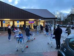 Kunder holdt avstand i køen som hadde dannet seg utenfor en Aldi-butikk i Hamburg alt før åpningstid lørdag. Foto: dpa via AP / NTB