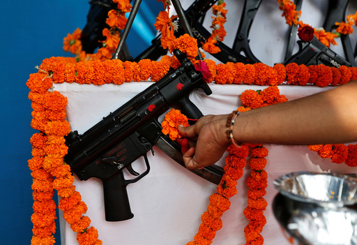 A Hindu priest offers prayers to a weapon as part of a ritual at the police headquarters on the occasion of Vijaya Dashmi or Dussehra festival in Ahmedabad