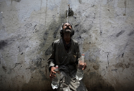 A man cools off from a public tap after filling bottles during intense hot weather in Karachi,