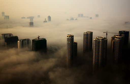 Buildings in construction are seen among mist during a hazy day in Rizhao