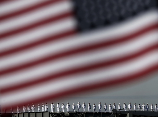 The crew members of the USS Ronald Reagan, a Nimitz-class nuclear-powered super carrier, saluting is seen behind the national flag of the U.S. as it arrives at the U.S. naval base in Yokosuka