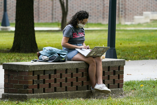 A masked student works on her laptop on the campus of Ball State University in Muncie, Ind., Thursday, Sept. 10, 2020. College towns across the U.S. have emerged as coronavirus hot spots in recent weeks as schools struggle to contain the virus. Out of nearly 600 students tested for the virus at Ball State, more than half have returned been found positive, according to data reported by the school. Dozens of infections have been blamed on off-campus parties, prompting university officials to admonish students.  (AP Photo/Michael Conroy)
