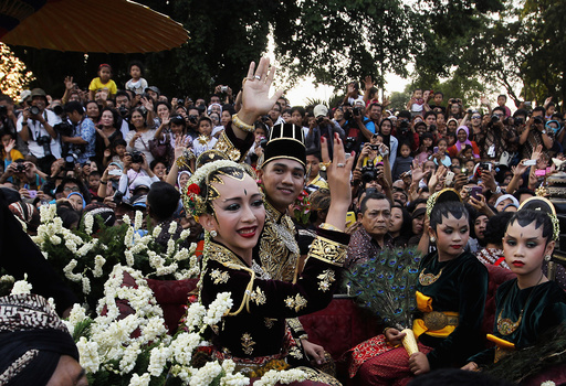KPH Yudanegara and his wife GKR Bendara wave to the crowd in a horse-drawn carriage in Yogyakarta