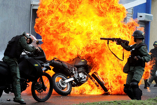 Riot security forces clash with demonstrators as a motorcycle is set on fire during a protest against Venezuelan President Nicolas Maduro's government in San Cristobal