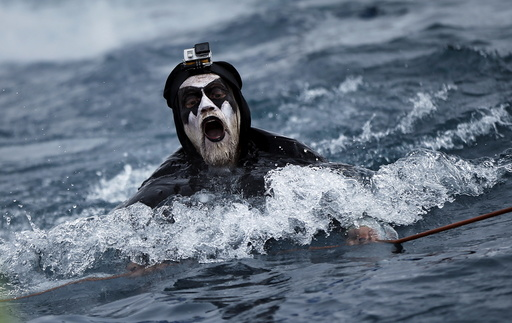 A participant swims after jumping during the Red Bull Jump and Freeze competition at the ski resort of Gudauri