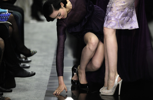 A model stumbles while presenting a creation by designer Bill Gaytten as part of his Spring/Summer 2012 collection for French fashion house Dior in Shanghai