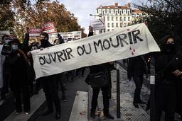 «Åpne eller dø» sto det på et banner da butikk- og restauranteiere demonstrerte i franske Lyon nylig. Lørdag får butikkene åpne igjen, men EU-topp Ursula von der Leyen advarer mot å åpne for raskt og risikere en ny smittebølge. Arkivfoto: Laurent Cipriani / AP / NTB
