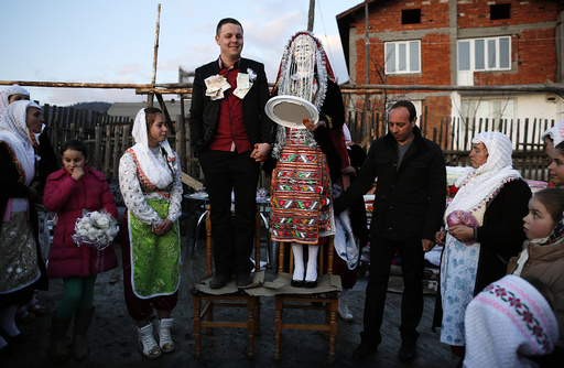 Bulgarian Muslims Azim and his bride Fikrie pose in front of their house during their wedding ceremony in Ribnovo