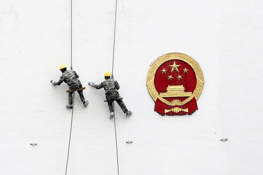 File picture of workers painting a wall of a government building in Hangzhou