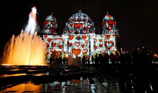People look at a light installation at the Berlin Cathedral during the opening day of the