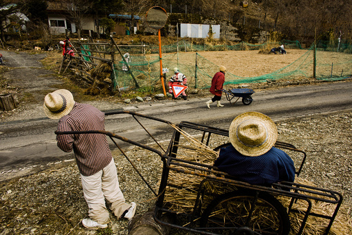 A woman pushes a wheelbarrow past scarecrows in the mountain village of Nagoro