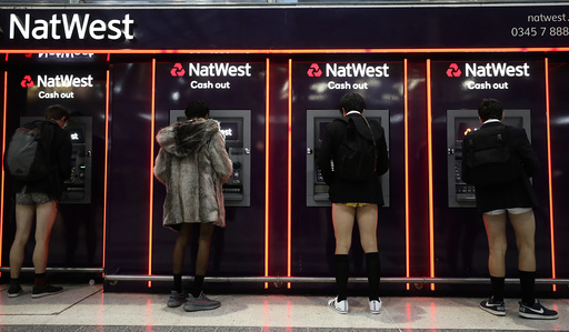 Passengers without trousers stand at cash machines as part of the 'No Trousers on the Tube Day' event, in London